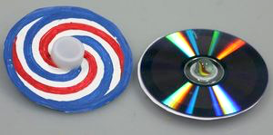 Decorated CDs made into spinners. Swirls of red, white, and blue stripes cover one CD. A bottle cap is used as a handle. Another CD is turned over to the shiny metalic data side.