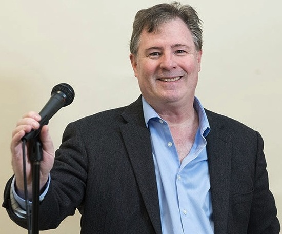 Dave Rattigan holding a microphone and smiling.