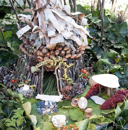A fairy house built among ivy. The walls are made from sticks and the roof is crafted from acorns and bark from a birch tree. Small pine cones ring the base of the house. Pebbles make up a walkway leading into the front yard.