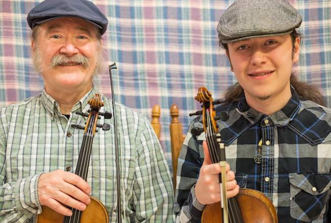 Two Thomson men smile in the photo. Each man is wearing a driver cap and plaid shirt. They are holding violins and bows.