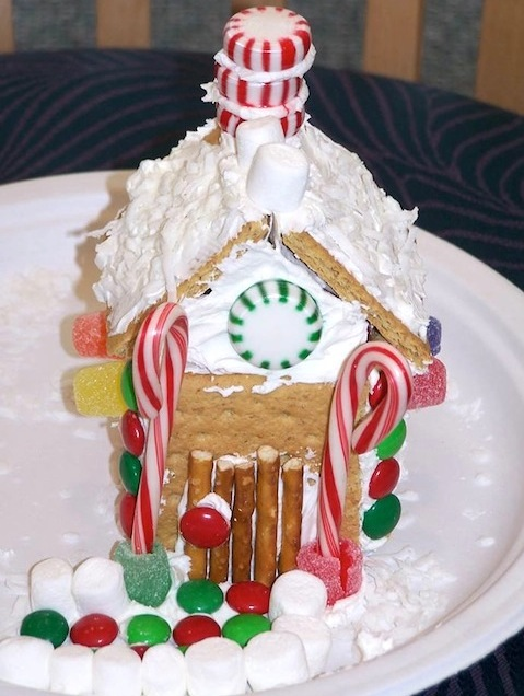 A gingerbread house with a frosted roof and a peppermint candy chimney. Candy canes frame the front door. Marshmallows and colored candy forms a front walkway.