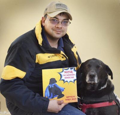 Don Jarvis and his service dog Mocha. Don smiles and holds a copy of his book: Mocha, The Superhero Service Dog. Mocha has black fur and a grey muzzle.