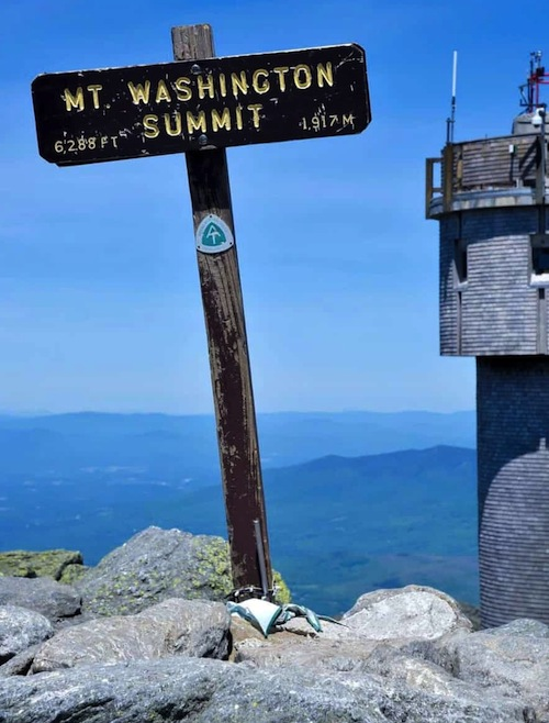 A mountain top sign reading: Mount Washington Summit, 6,288 feet, 1917 meters. A circular metal weather tower is off to the right. Clear blue sky and distant mountain peaks are in the background.