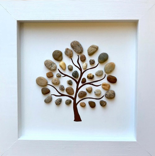 Frame pebble art piece. Pebbles make up the leaves of a tree. The trunk is painted in black.